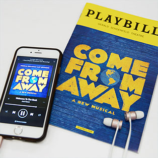 Thumbnail image of Come From Away's Playbill and Come From Away album playing on smartphone with headphones